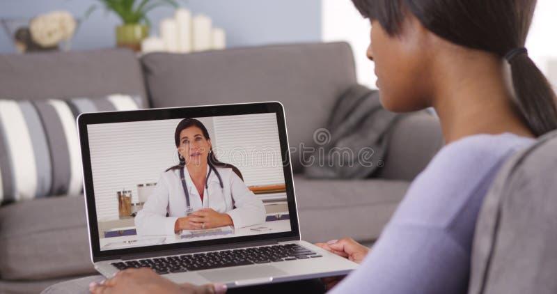 Mujer africana que habla con el doctor en línea fotografía de archivo