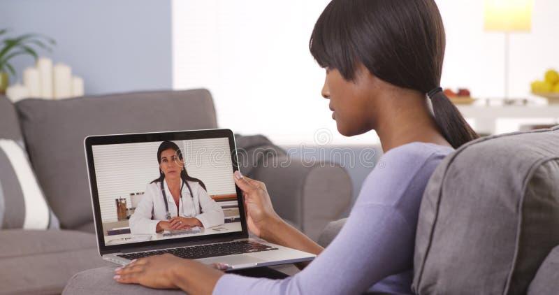 Mujer africana que habla con el doctor en línea foto de archivo libre de regalías