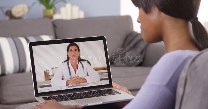 Mujer africana que habla con el doctor en línea fotografía de archivo libre de regalías