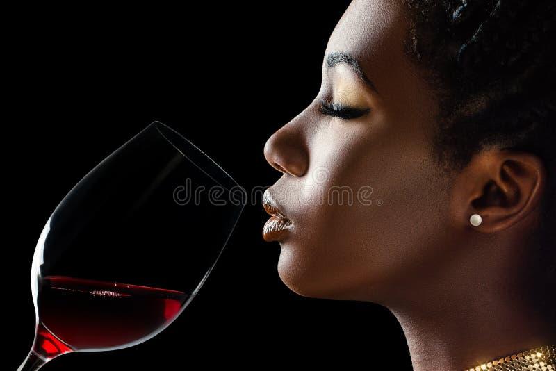 Mujer africana que huele el aroma del vino rojo fotografía de archivo