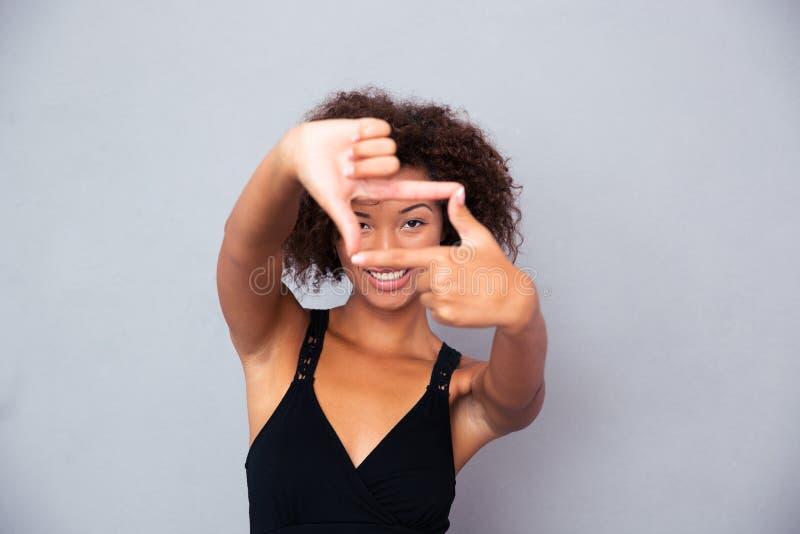 Mujer africana que mira la cámara con gesto del marco imagenes de archivo