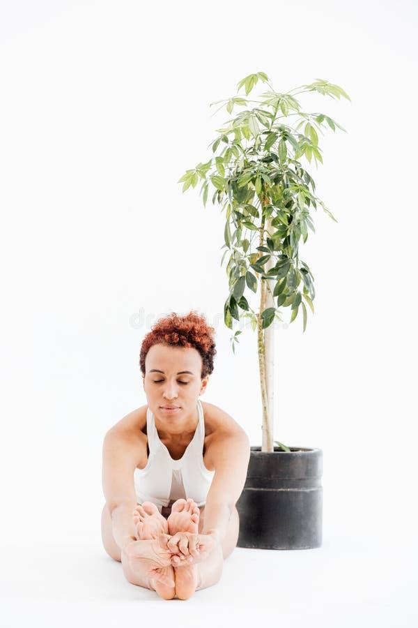 Mujer africana que se sienta cerca de árbol en pote y que hace yoga imagen de archivo