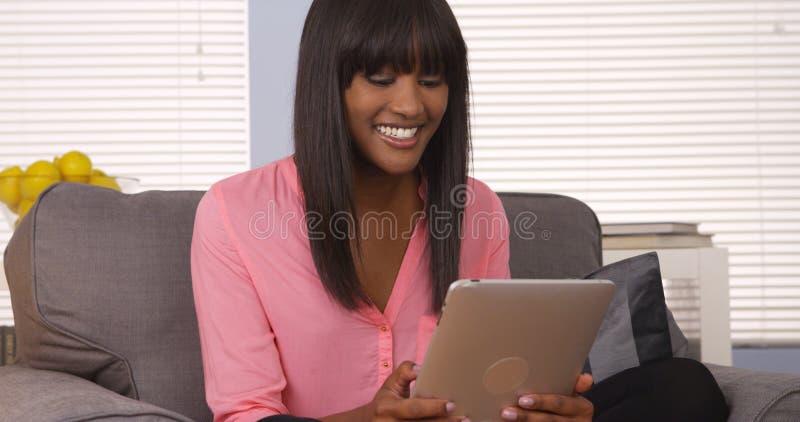 Mujer africana que usa el cojín en el sofá fotos de archivo libres de regalías