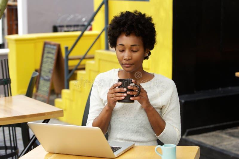 Mujer africana relajada que come un café en el café de la acera fotografía de archivo libre de regalías