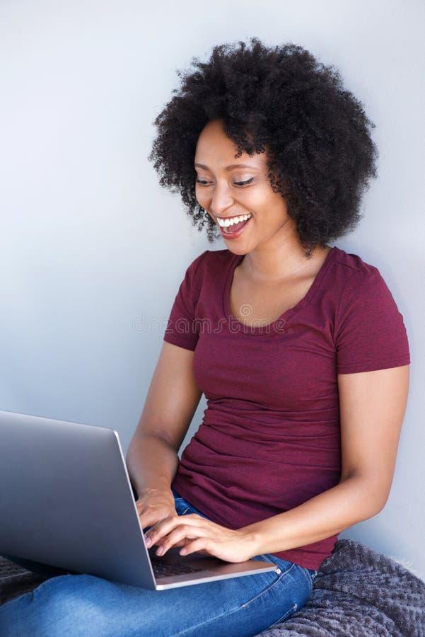 Mujer africana relajada que se sienta en casa y que trabaja en el ordenador portátil fotografía de archivo libre de regalías