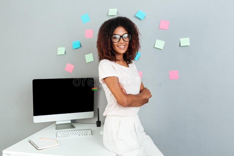 Mujer africana sonriente en las lentes que se colocan cerca de la tabla imagen de archivo libre de regalías