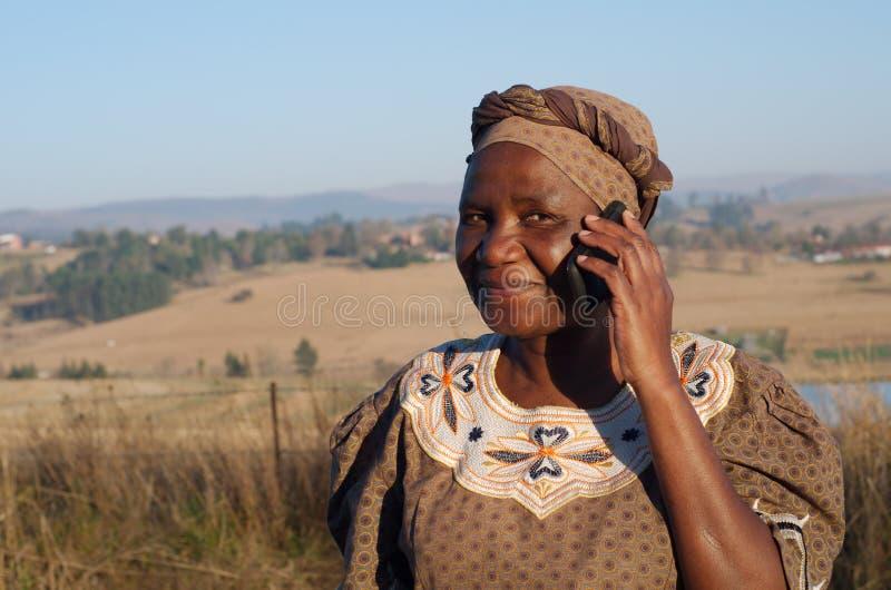Mujer africana tradicional del Zulú que habla en el teléfono móvil fotografía de archivo