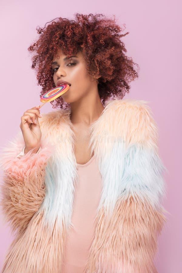 Mujer afro de moda con la piruleta en fondo rosado foto de archivo libre de regalías