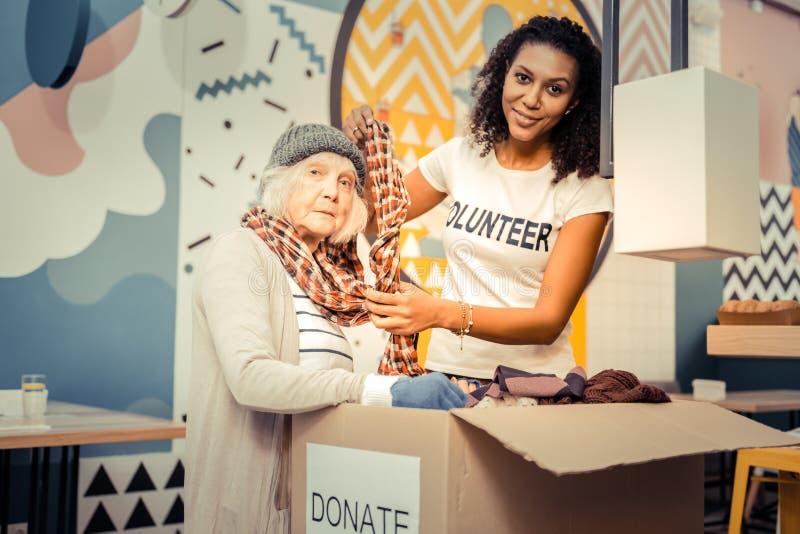 Mujer afroamericana agradable que ayuda a llevar una bufanda foto de archivo libre de regalías