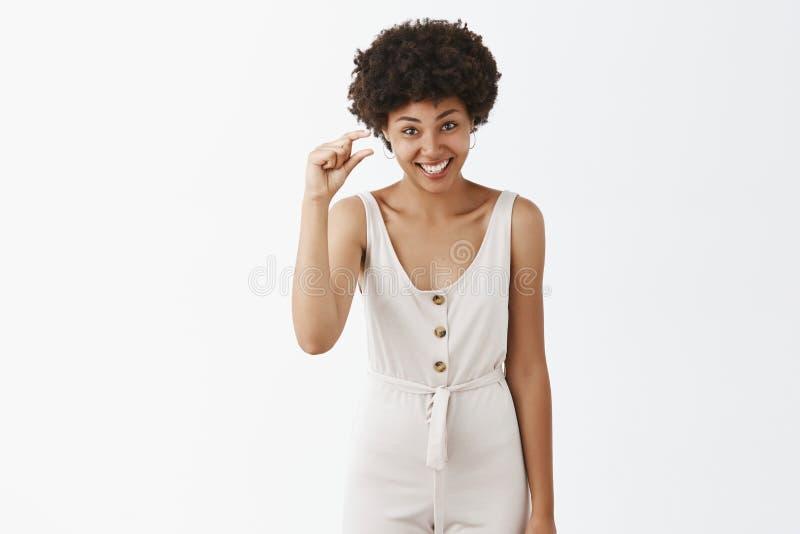 Mujer afroamericana apuesta divertida y emotiva con el peinado rizado en los guardapolvos blancos que muestran algo minúsculo imagenes de archivo