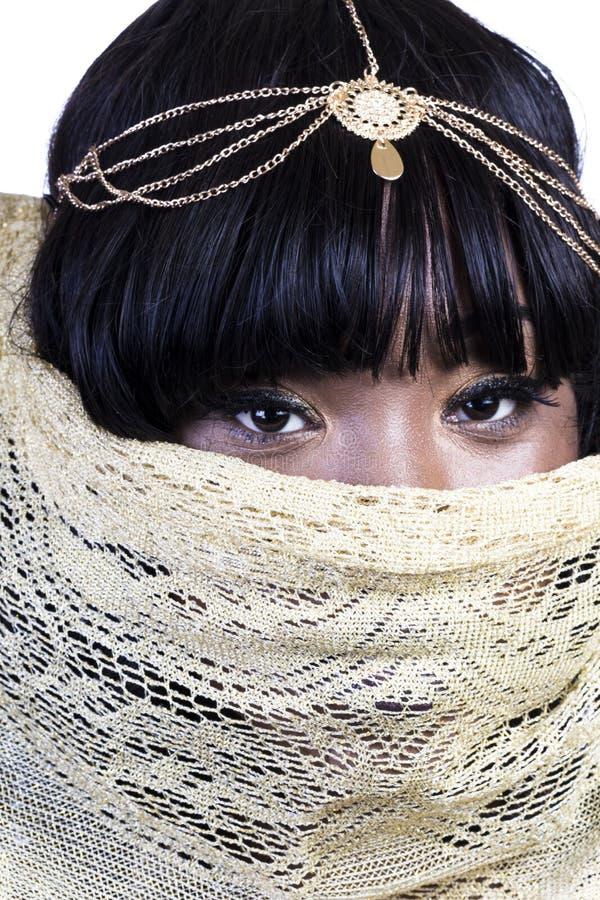 Mujer afroamericana atractiva con la cara de la cubierta de paño del oro fotos de archivo libres de regalías
