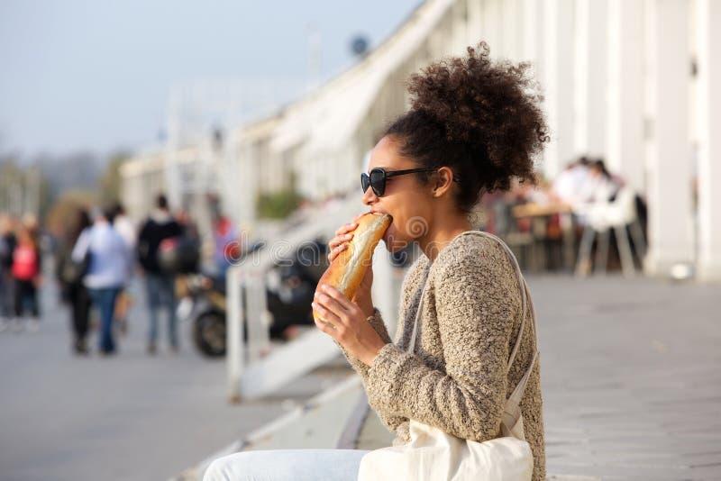 Mujer afroamericana atractiva que come la comida al aire libre fotos de archivo