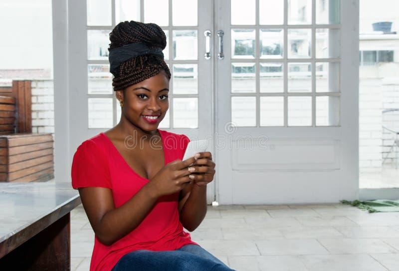 Mujer afroamericana atractiva que envía el mensaje con el teléfono fotografía de archivo