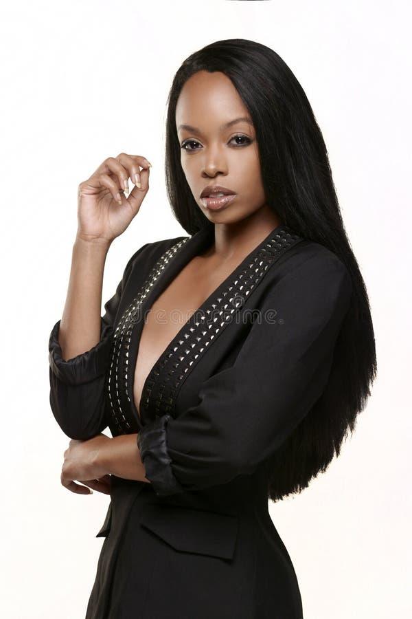 Mujer afroamericana atractiva que lleva una chaqueta negra tachonada imagenes de archivo