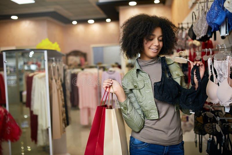 Mujer afroamericana atractiva sonriente de los jóvenes que elige talla de sujetador correcta en boutique de la tienda de la ropa  fotografía de archivo