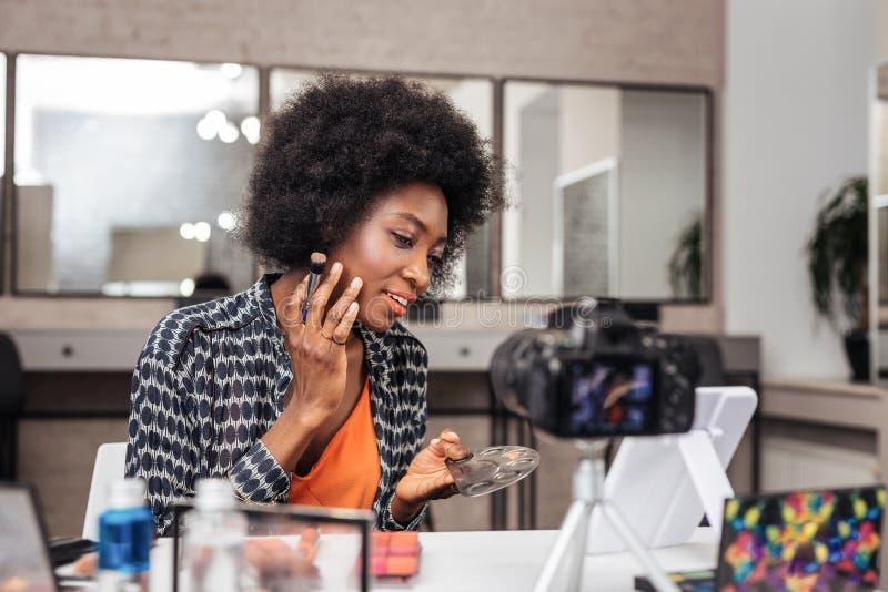 Mujer afroamericana bonita con el pelo rizado que intenta un nuevo lápiz corrector fotografía de archivo libre de regalías
