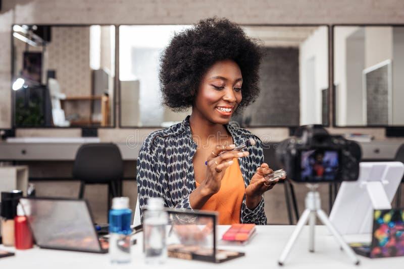 Mujer afroamericana bonita con el pelo rizado que parece interesado imágenes de archivo libres de regalías