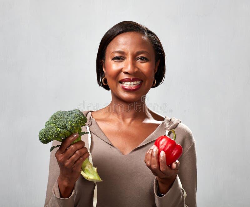 Mujer afroamericana con bróculi imagen de archivo libre de regalías