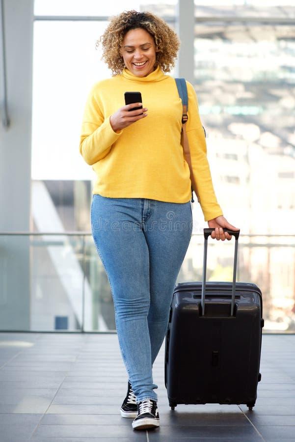 Mujer afroamericana con curvas que camina con la maleta y el teléfono móvil fotografía de archivo libre de regalías