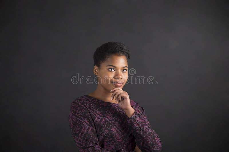 Mujer afroamericana con la mano en la barbilla que piensa en fondo de la pizarra imágenes de archivo libres de regalías