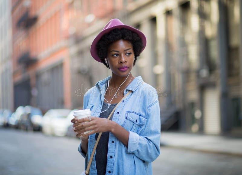 Mujer afroamericana de moda que escucha la música y el enjoyi foto de archivo libre de regalías