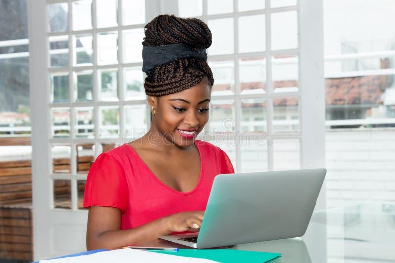 Mujer afroamericana de risa que hace compras en línea fotos de archivo libres de regalías