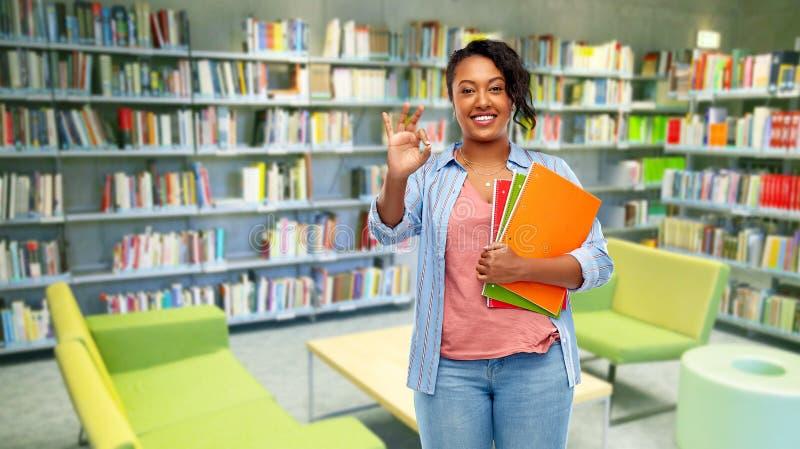 Mujer afroamericana del estudiante en la biblioteca foto de archivo
