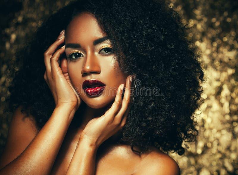 Mujer afroamericana elegante joven con el pelo afro Maquillaje del encanto Fondo de oro foto de archivo