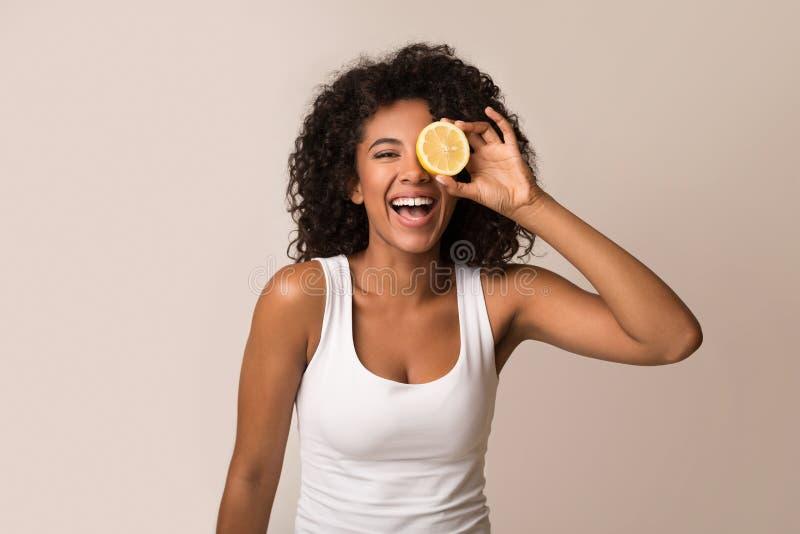 Mujer afroamericana emocionada que lleva a cabo la mitad del limón fotos de archivo