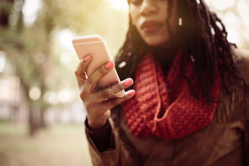 Mujer afroamericana en parque usando el teléfono elegante fotos de archivo