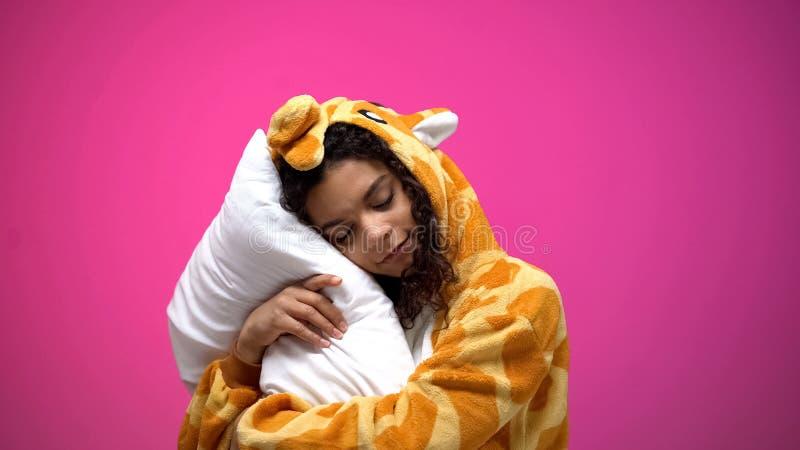 Mujer afroamericana en pijamas de la jirafa que duerme y que sonr?e, comodidad de sensaci?n foto de archivo libre de regalías