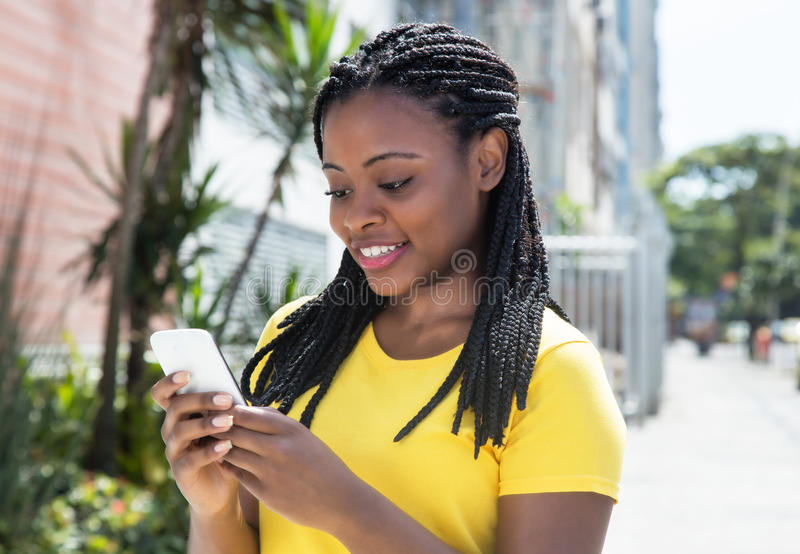 Mujer afroamericana en un mensaje que manda un SMS de la camisa amarilla con el teléfono móvil foto de archivo