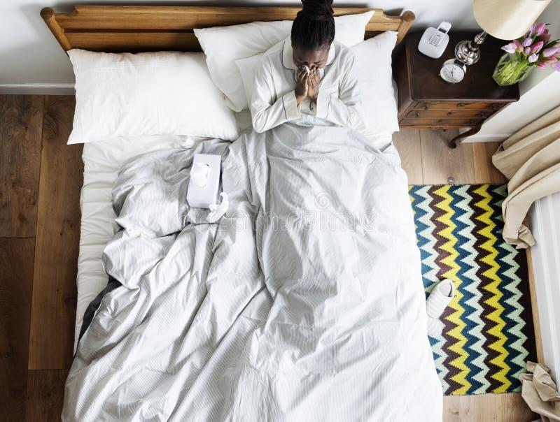 Mujer afroamericana enferma en la cama que sopla su nariz fotografía de archivo