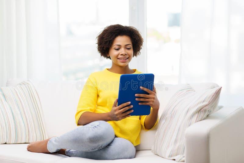 Mujer afroamericana feliz con PC de la tableta foto de archivo