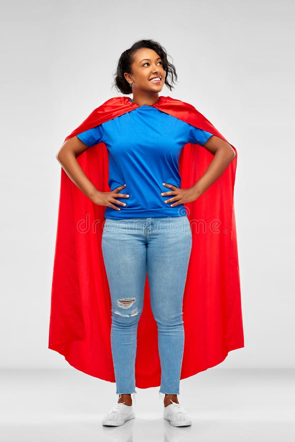 Mujer afroamericana feliz en cabo rojo del super héroe fotos de archivo