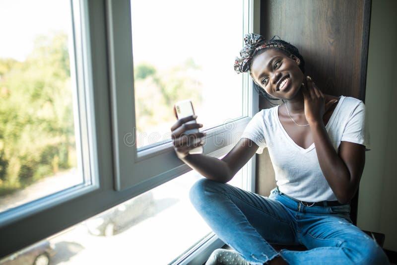 Mujer afroamericana feliz en la camiseta que se sienta en el alf?izar y que hace el selfie en el tel?fono mientras que agita en l imagen de archivo libre de regalías