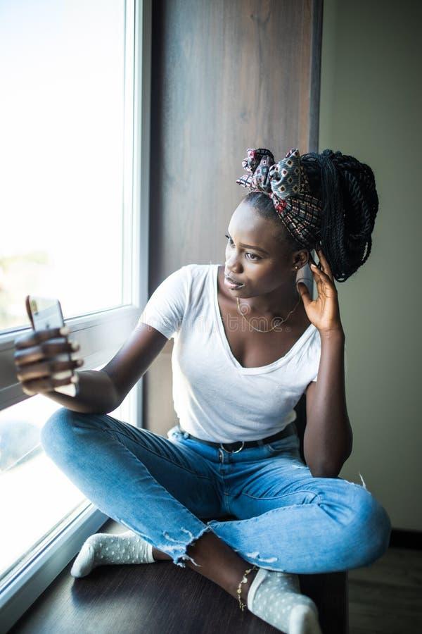 Mujer afroamericana feliz en la camiseta que se sienta en el alf?izar y que hace el selfie en el tel?fono mientras que agita en l fotografía de archivo