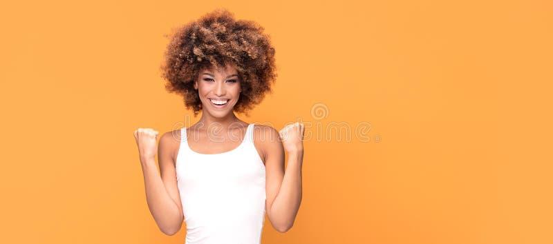 Mujer afroamericana feliz hermosa que celebra la victoria imagenes de archivo