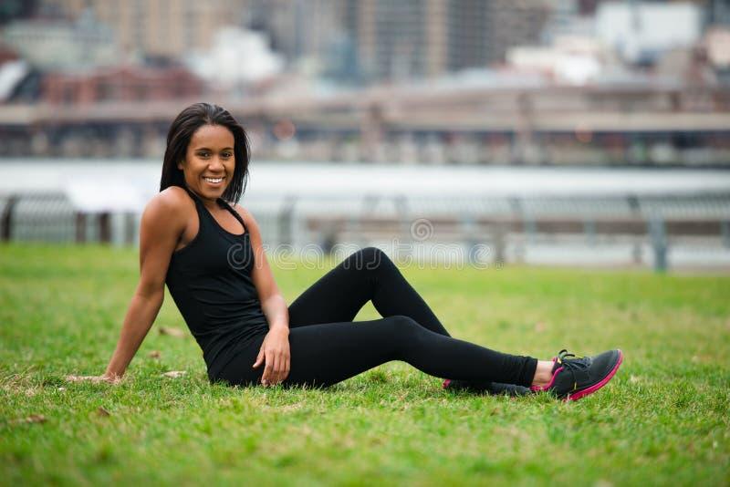 Mujer afroamericana feliz hermosa que se sienta en la hierba verde en parque de la ciudad después de ropa del deporte del entrena imagenes de archivo