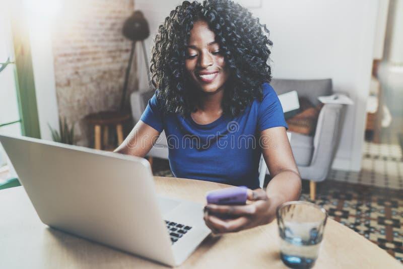 Mujer afroamericana feliz que usa el ordenador portátil y el smartphone mientras que se sienta en la tabla de madera en la sala d imagen de archivo libre de regalías