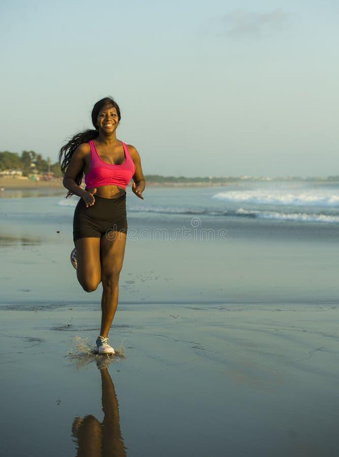 Mujer afroamericana feliz y atractiva joven del corredor que ejercita en entrenamiento corriente en la playa hermosa que activa y imagenes de archivo