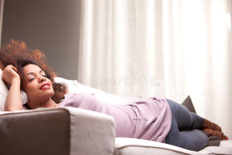 Mujer afroamericana hermosa en un sofá imagen de archivo
