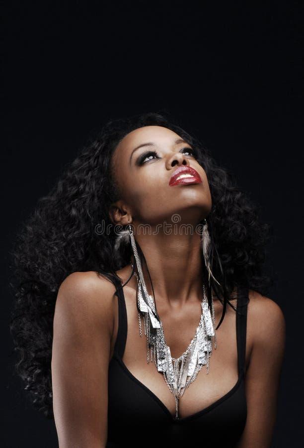 Mujer afroamericana hermosa que mira hacia arriba foto de archivo