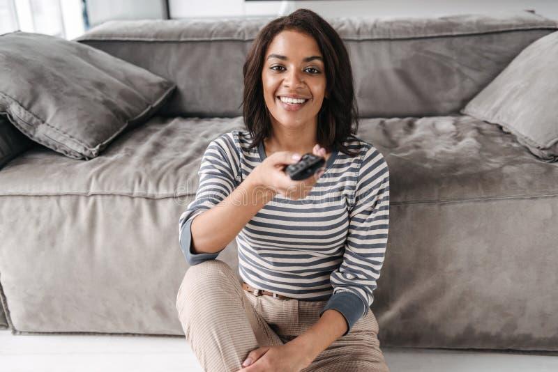 Mujer afroamericana joven atractiva que se sienta en un sofá fotos de archivo