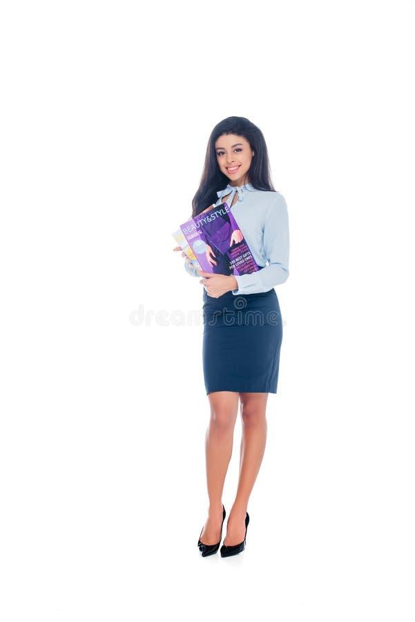 mujer afroamericana joven atractiva que sostiene las revistas de la belleza y que sonríe en la cámara aislada fotografía de archivo