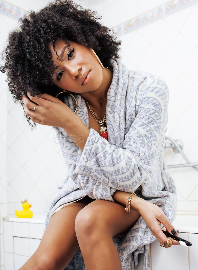 Mujer afroamericana joven de la belleza en albornoz con el cepillo de dientes que toma el cuidado de sí misma, concepto de la mañ imagen de archivo