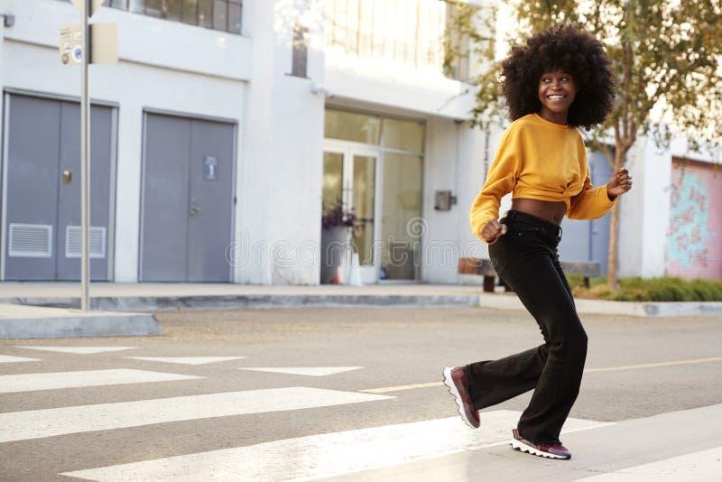 Mujer afroamericana joven de moda con el pelo afro que corre a través de la calle, integral, cierre para arriba fotos de archivo libres de regalías