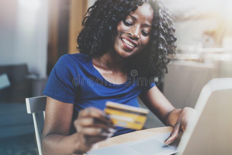 Mujer afroamericana joven feliz que hace compras en línea a través del ordenador portátil usando tarjeta de crédito en casa Horiz imágenes de archivo libres de regalías
