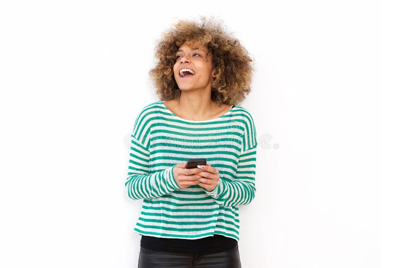 Mujer afroamericana joven feliz que ríe con el fondo blanco que se rebaja del teléfono móvil fotografía de archivo libre de regalías