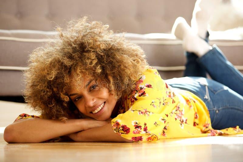 Mujer afroamericana joven hermosa que miente en piso en casa y la sonrisa imagen de archivo libre de regalías